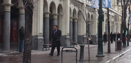 Businessman Walking by Pillars